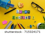 Small photo of Word LEARN ENGLISH made with carved letters onyellow desk with office or school supplies, stationery. Concept of English language courses
