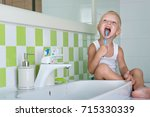 small boy brushing teeth in the ... | Shutterstock . vector #715330339