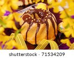marble ring cake  poured with chocolate on easter table in purple color and yellow forsythia flowers around - stock photo