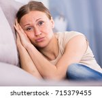 Small photo of Portrait of sad woman sitting on sofa in home interior