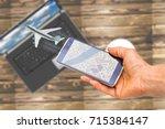 hand holding smartphone on... | Shutterstock . vector #715384147
