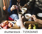 hands holding tea cups clinking ... | Shutterstock . vector #715426465