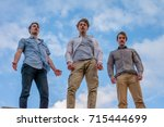 Small photo of Low angle photo of three guys standing high above, looking down, dramatic vantage point, cinematic look