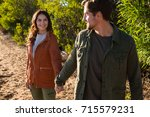 smiling young couple looking... | Shutterstock . vector #715579231