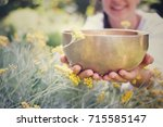 hands holding a singing bowl. | Shutterstock . vector #715585147