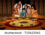 family sitting near rangoli   | Shutterstock . vector #715623361