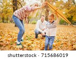 mother and father playing with... | Shutterstock . vector #715686019