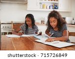 two sisters sitting at table in ... | Shutterstock . vector #715726849