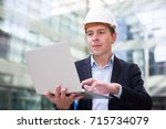 cheerful male builder talking... | Shutterstock . vector #715734079