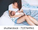 mother breastfeeding baby in... | Shutterstock . vector #715764961