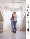 Small photo of Rear View Of Affectionate Couple Standing By Bedroom Window