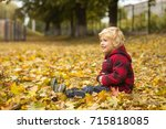 cute blond boy walks in autumn... | Shutterstock . vector #715818085