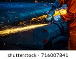 the steel worker is burnishing... | Shutterstock . vector #716007841