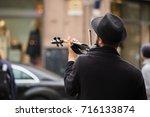a street musician playing the... | Shutterstock . vector #716133874