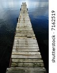 Dock floating in blue lake with water ripples around - stock photo