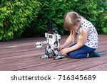 little schoolgirl plays on the... | Shutterstock . vector #716345689