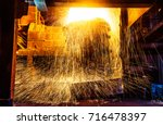 sparks of molten steel dash in... | Shutterstock . vector #716478397