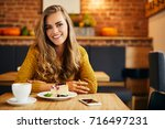 gorgeous young woman looking at ... | Shutterstock . vector #716497231