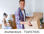 moving in a new home. carrying... | Shutterstock . vector #716517631