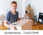 moving day. young man carrying... | Shutterstock . vector #716517649