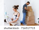 young couple in love moving in... | Shutterstock . vector #716517715