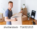 moving day. young man carrying... | Shutterstock . vector #716521315