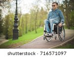 Small photo of young disabled man in wheelchair walking park
