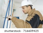 worker drilling on the wall | Shutterstock . vector #716609425