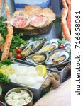 Small photo of scallops oyster Alaska crab and raw shelled mussels on ice background