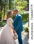 the bride and groom in the park.... | Shutterstock . vector #716660779