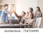 happy business team giving hi... | Shutterstock . vector #716723494