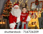 Small photo of Happy little boy sitting on Santa's lap in room with beautiful Christmas decorations