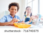 modern schoolkids eating snacks ... | Shutterstock . vector #716740375