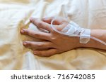 woman hand with iv line. | Shutterstock . vector #716742085