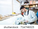 wood turning on a lathe at a... | Shutterstock . vector #716748325