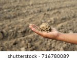 hand holding dried soil with... | Shutterstock . vector #716780089
