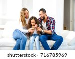 young parents sitting on the...   Shutterstock . vector #716785969