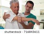 man having chiropractic arm...   Shutterstock . vector #716843611