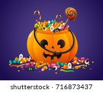 Stock vector halloween pumpkin basket full of candies and sweets on violet background 716873437