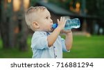 funny kid 1 year is drinking... | Shutterstock . vector #716881294