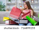 young woman with shopping bags... | Shutterstock . vector #716899255