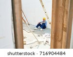 tired young construction worker ... | Shutterstock . vector #716904484