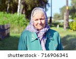 an old woman in a scarf.... | Shutterstock . vector #716906341