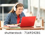 happy student listening a video ... | Shutterstock . vector #716924281