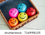 Self Made Hand Drawn - Group of emotional balls: happy Smiley face on yellow, pink and orange ball. Sad face on blue ball and mad face on red ball. They are in a basket - Vintage Film Filter