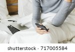 woman is using mobile on the bed | Shutterstock . vector #717005584
