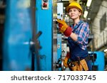 pretty young machine operator... | Shutterstock . vector #717033745
