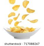 tasty potato chips falling onto ... | Shutterstock . vector #717088267