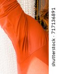 Small photo of Woman having sweat stains on orange shirt with long sleeve. Diaphoresis problem concept.