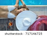 glad girl in a white swimsuit... | Shutterstock . vector #717146725